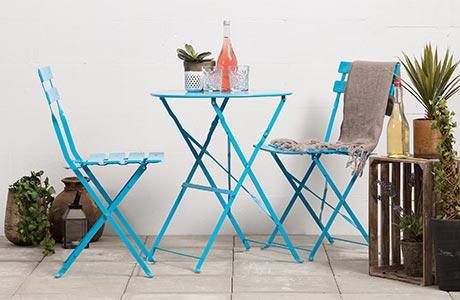 Litet balkongbord och två stolar i blått stål